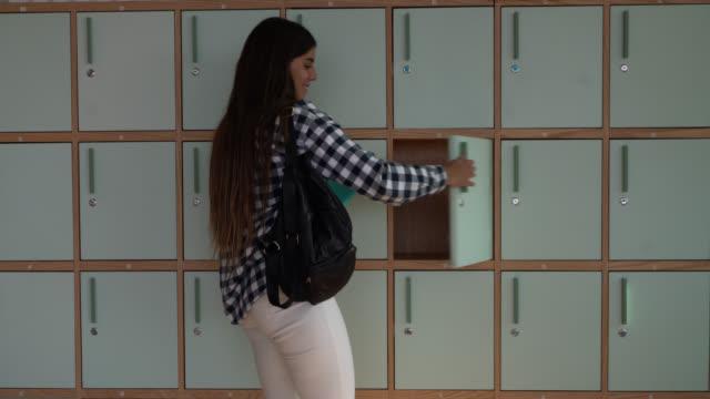 vídeos de stock, filmes e b-roll de mulher bonita alegre que põr afastado sua trouxa no cacifo no escritório - armário com fechadura