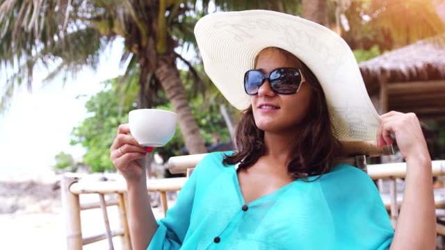 vídeos de stock e filmes b-roll de cheerful beautiful woman wearing hat and sunglasses on holiday, sitting in beach cafe with scenic views of the sea and palm trees drinks tea has a breakfast. slow motion. 3840x2160 - algarve