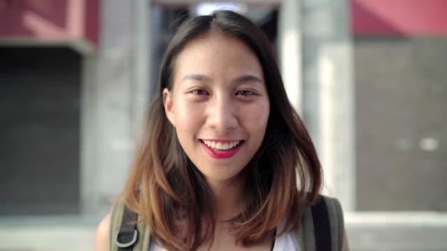 Cheerful beautiful young Asian backpacker woman feeling happy smiling to camera while traveling at Chinatown in Beijing, China. Lifestyle backpack tourist travel holiday concept.