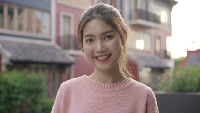 glad vacker ung asiatisk kvinna känner sig lycklig leende till kameran när du reser på chinatown i peking, kina. livsstil ryggsäck turist resa semester koncept. porträtt tittar på kamera. - kinesiskt ursprung bildbanksvideor och videomaterial från bakom kulisserna