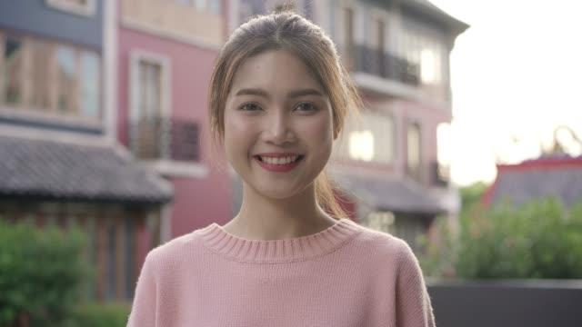 中国の北京のチャイナタウンで旅行しながら、陽気な美しい若いアジアの女性は、カメラに微笑んで幸せを感じています。ライフスタイルバックパック観光旅行の休日の概念。カメラを見て� - スーパーモデル点の映像素材/bロール