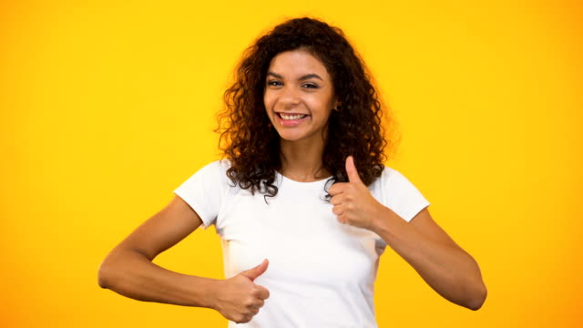 Cheerful biracial woman showing thumbs-up and smiling against yellow background Cheerful biracial woman showing thumbs-up and smiling against yellow background representing stock videos & royalty-free footage