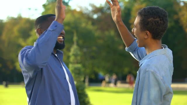neşeli siyah kardeşler yüksek beş açık, mutlu aile, yakın ilişkiler veren - uzun fiziksel özellikler stok videoları ve detay görüntü çekimi