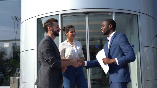 Cheerful black salesman handing the keys to customer couple at a car dealership shaking hands all smiling