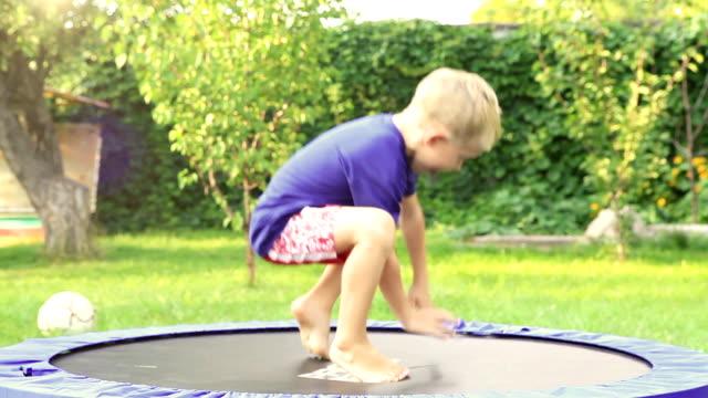 cheerful blond boy jumping on trampoline in the summer garden - gym skratt bildbanksvideor och videomaterial från bakom kulisserna