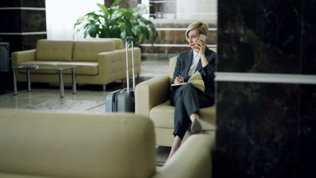 Cheerful blonde businesswoman sitting in armchair in hotel lobby talking on mobile phone and writing in notepad smiling and looking aside. Business, travel and people concept Attractive cheerful businesswoman sitting in armchair in hotel lobby talking on mobile phone and writing in notepad smiling and looking aside. Business, travel and people concept lounge chair stock videos & royalty-free footage