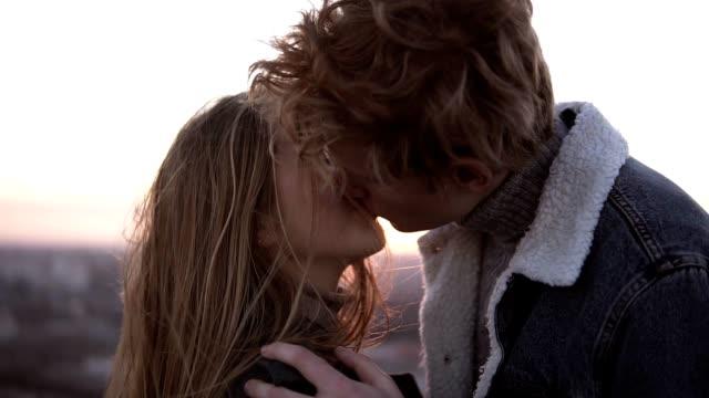 stockvideo's en b-roll-footage met vrolijke, blonde liefdevolle jonge koppel genieten van een romantische kus, terwijl staande op de winderige hoge dak met een stedelijke achtergrond - zoen