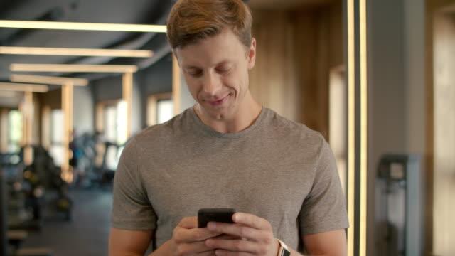 stockvideo's en b-roll-footage met vrolijke bodybuilder die zich bij gymnastiek bevindt. sportsman sms'te in sportclub - call center
