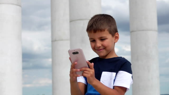 Cheerful boy is watching at the phone in his hands on the background of columns