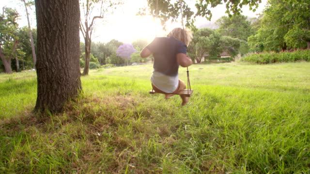 fröhliche junge spielt auf schaukel im park ein sonnenuntergang - kind schaukel stock-videos und b-roll-filmmaterial
