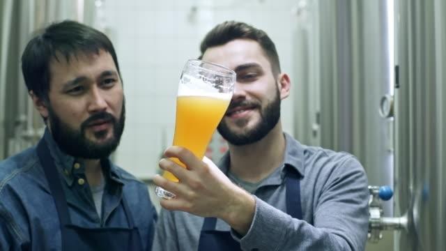 新鮮なビールを議論する陽気な醸造所労働者 - 醸造所点の映像素材/bロール