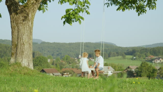 SLOW MOTION: Cheerful brother and sister chatting and swinging on fun summer day