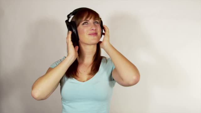 SLOW MOTION: Cheerful brunette dancing to funky music from headphones video