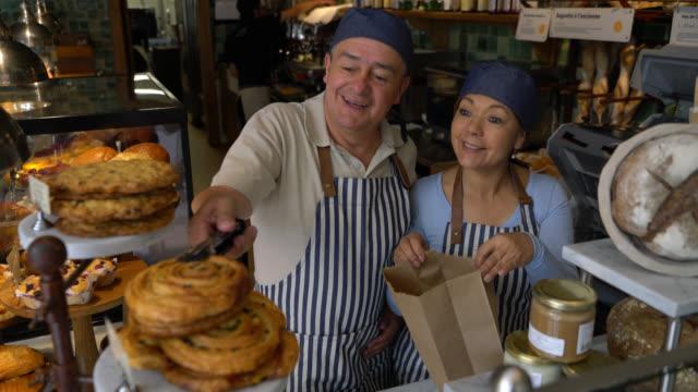 vidéos et rushes de propriétaires d'affaires joyeux d'une boulangerie préparant une commande de prise ajoutant des biscuits et des pâtisseries à un sac en papier - boulanger