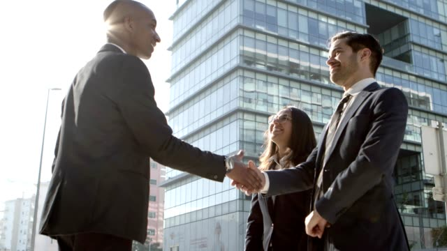 Cheerful business people shaking hands outdoors Cheerful business people shaking hands outdoors. Low angle view of multiethnic young business colleagues greeting each other and shaking hands on street. Business meeting concept business handshake stock videos & royalty-free footage