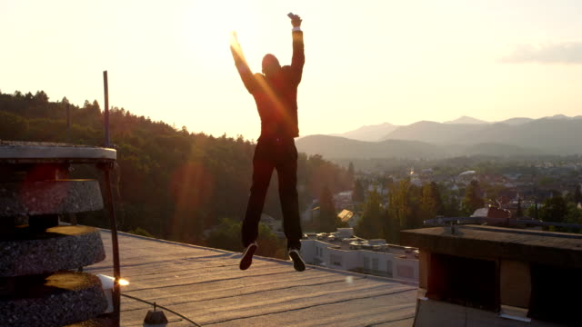 CLOSE UP: Cheerful businessman jumping with hands raised on rooftop at sunset SLOW MOTION CLOSE UP DOF: Excited entrepreneur jumping for joy raising hands when successfully closing big business deal. Happy man rejoicing and leaping on the rooftop at amazing golden light sunrise good news stock videos & royalty-free footage