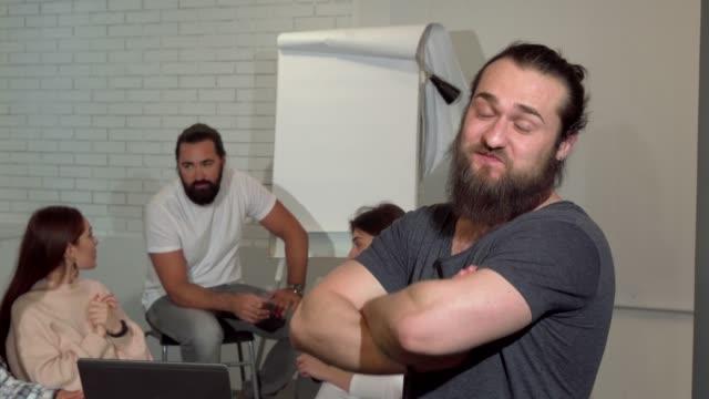 Alegre hombre de negocios sonriendo a la cámara, sus colegas hablando en la parte posterior - vídeo