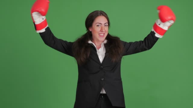 cheerful businesswoman in boxing gloves on green background video