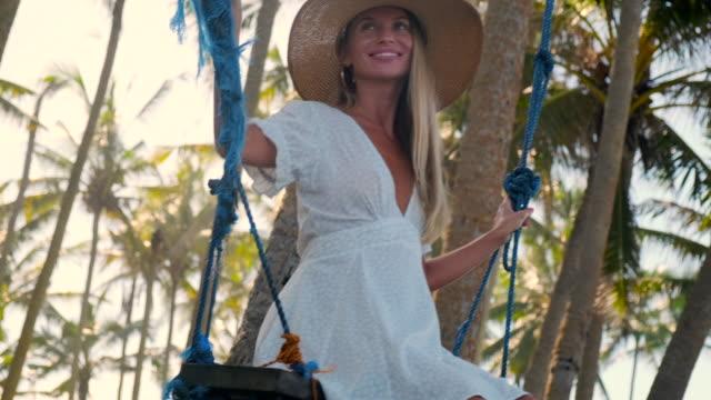 vídeos y material grabado en eventos de stock de mujer alegre despreocupada en columpios relajantes durante las vacaciones en trópicos - disquete