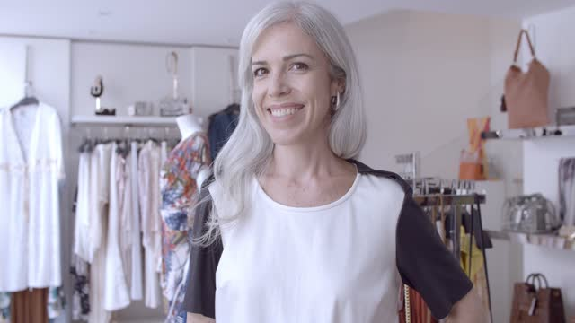 Cheerful Caucasian fair haired woman posing in fashion store Cheerful Caucasian fair haired woman posing in fashion store, looking at camera, smiling. Front view, headshot. Boutique customer or shop assistant concept physical position stock videos & royalty-free footage