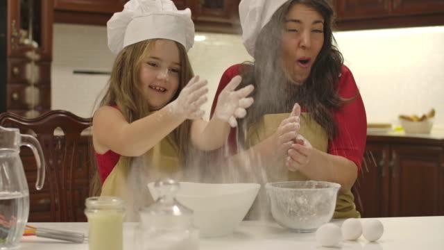 glad kaukasiska mor och dotter matlagning tillsammans i köket. liten flicka klappar händer och mjöl flyger runt. lycklig familj skrattar medan du bakar hemma. cinema 4k film prores hq. - enbarnsfamilj bildbanksvideor och videomaterial från bakom kulisserna