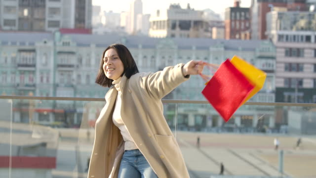 Cheerful Caucasian woman dancing with colorful shopping bags and singing. Happy shopaholic enjoying purchases on city street. Shopaholism, lifestyle. Cinema 4k ProRes HQ.