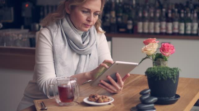 vídeos de stock e filmes b-roll de cheerful caucasian woman drinking tea and using tablet - senior business woman tablet