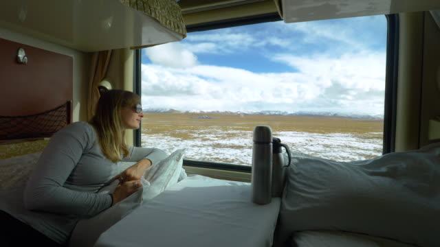 vídeos y material grabado en eventos de stock de cerca: mujer caucásica alegre mira por la ventana de su cabina de primera clase - viaje en primera clase