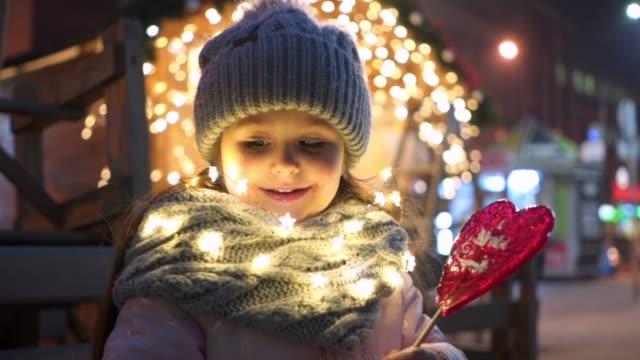 fröhliches kind genießen ein herz geformt lutscher in der weihnachtszeit - weihnachtsmarkt stock-videos und b-roll-filmmaterial