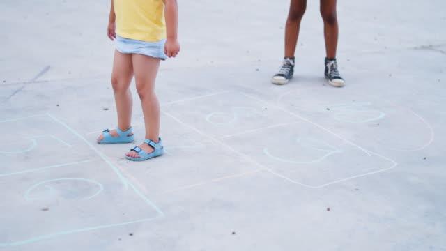 stockvideo's en b-roll-footage met vrolijk kind spelen hinkelspel - peuterklasleeftijd