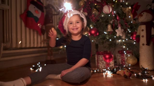 Cheerful child with Santa hat having fun with sparklers Lovely and beautiful toddler girl enjoying her time at home, playing with sparklers next to a Christmas tree. christmas fun stock videos & royalty-free footage
