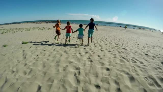 Cheerful children in bright clothes are running on the sandy beach to the sea