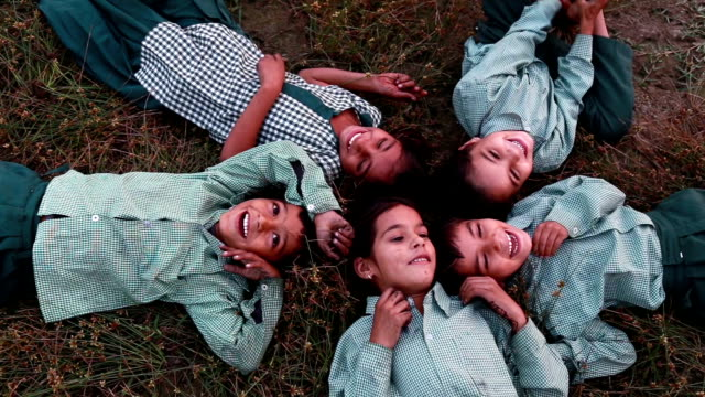 cheerful children lying dawn on grass HD1080p: Group of cheerful children wearing school uniform lying on grass & laughing elevated view. indian family stock videos & royalty-free footage