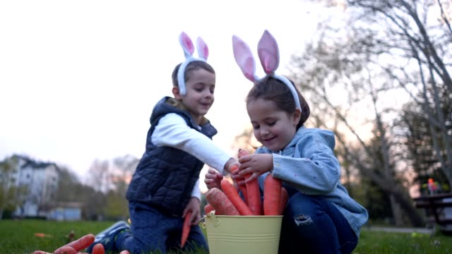 fröhliche kinder, die zu ostern in einem park spielen - karotte peace stock-videos und b-roll-filmmaterial