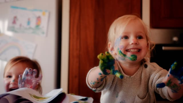Cheerful children with dirty hands painting with acrylic paints