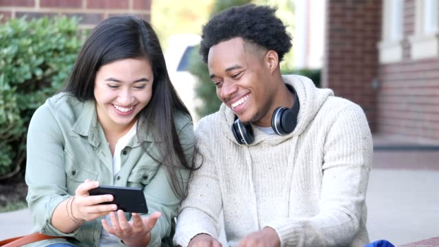cheerful college couple watch something on smartphone - compagni scuola video stock e b–roll