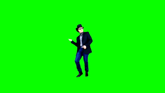 cheerful cool cowboy in a hat and in sunglasses is dancing jokingly on chroma key. actor performing on the green background. - kapelusz kowbojski filmów i materiałów b-roll