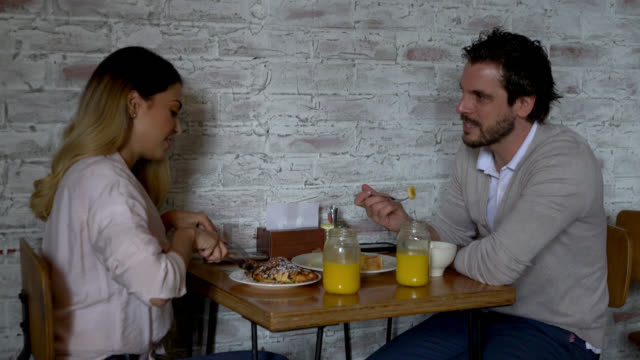 cheerful couple at a cafe enjoying breakfast while talking - cucina francese video stock e b–roll