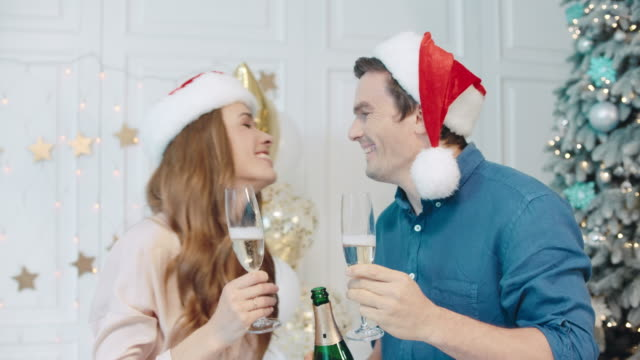 Cheerful couple drinking champagne near christmas tree