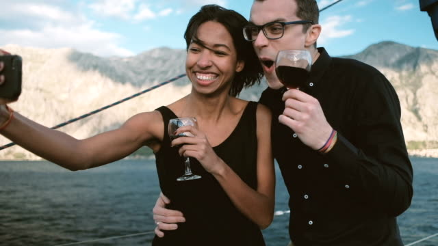 Cheerful couple drinking wine and making funny selfie phone video
