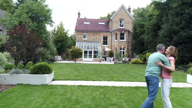 Cheerful couple embracing in garden and looking at their large detached house video