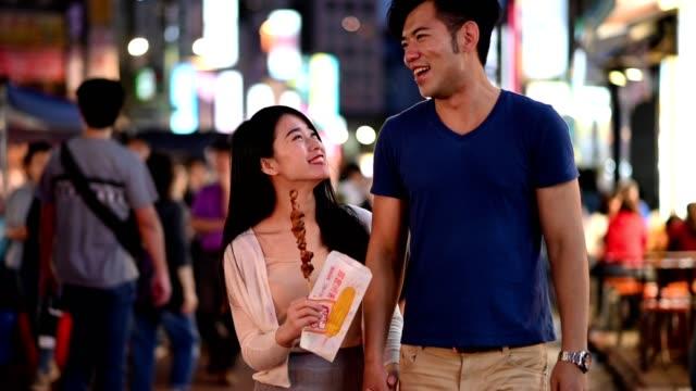 Cheerful couple enjoying a night market