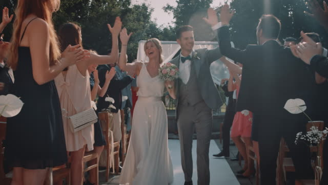 Cheerful couple giving high-five to wedding guests Minister cheering for married young couple. Happy bride and bridegroom giving high-five to guests while walking on aisle. They are enjoying during wedding celebration at church. newlywed stock videos & royalty-free footage