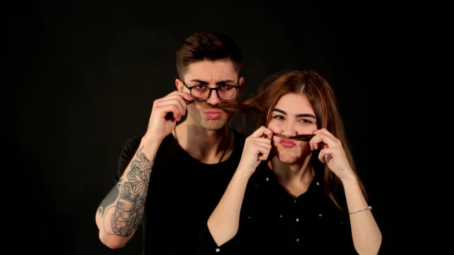 a cheerful couple makes a mustache out of hair. - brunette woman eyeglasses kiss man video stock e b–roll