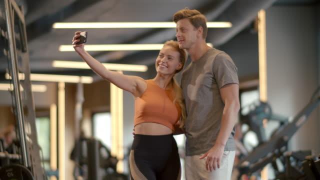 stockvideo's en b-roll-footage met vrolijk paar dat selfiefoto maakt bij gymnastiek. het paar dat van de geschiktheid in sportclub stelt - call center