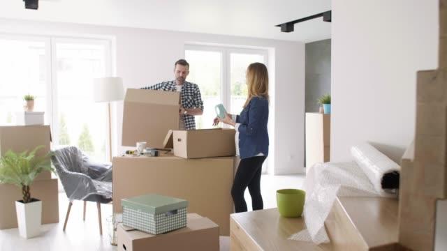 glad par flyttar i den nya lägenheten - omlokalisering bildbanksvideor och videomaterial från bakom kulisserna