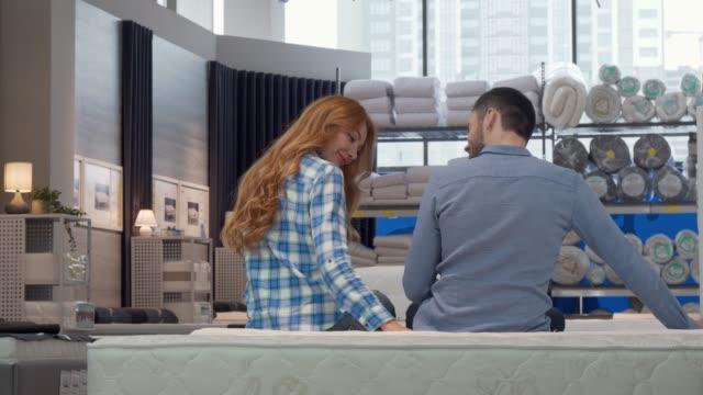 vídeos y material grabado en eventos de stock de pareja alegre sonriendo a la cámara, mientras que la elección de la cama nueva en la tienda de muebles - colchón