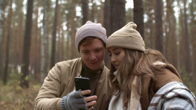 Bидео Cheerful Couple Using Smartphone and Chatting in Forest on Autumn Day