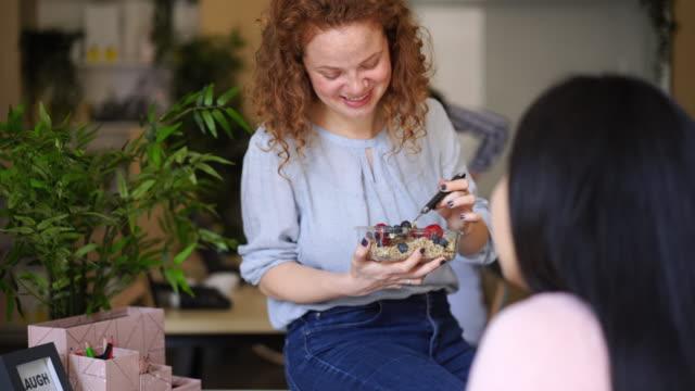 職場で朝食をとる陽気な巻き毛の女性 - おやつ点の映像素材/bロール