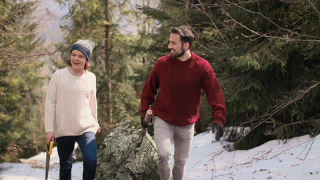 Cheerful dad and his son carrying heavy christmas tree